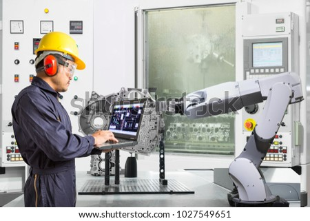 Engineer using laptop computer control automatic robotic hand with CNC machine in automotive industry, Smart factory concept #1027549651