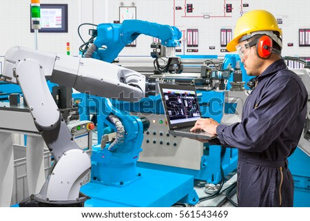 Engineer using laptop computer for maintenance automatic robotic hand machine tool at the factory