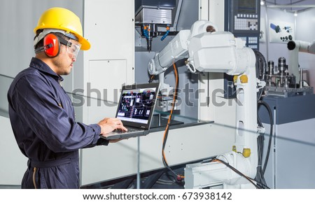 Engineer using laptop computer for maintenance automatic robotic hand machine tool in automotive industry #673938142
