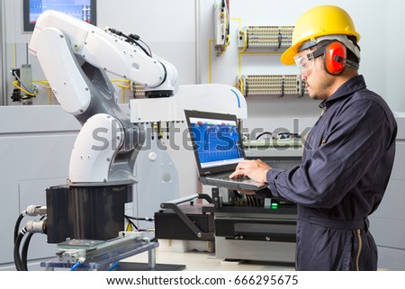 Engineer using laptop computer for maintenance automatic robotic hand machine tool in smart factory, Industry 4.0 concept #666295675
