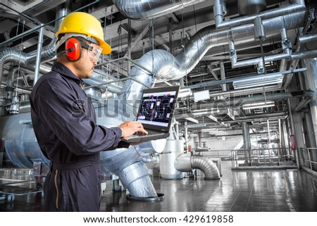 Engineer using laptop computer in thermal power plant factory