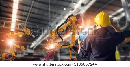 Engineer using tablet check and control automation robot arms machine in intelligent factory industrial on monitoring system software. Welding robotics and digital manufacturing operation.