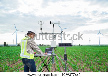 Engineer using tablet computer collect data with meteorological instrument to measure the wind speed, temperature and humidity and solar cell system on corn field background, Smart agriculture concept