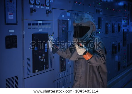 Photo of  Engineer wear a arc flash protection suit for inspection electrical current   and checking status switch gear electrical energy distribution substation.