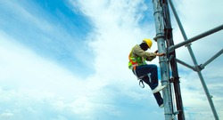 Engineer wear safety equipment and climb high telecom tower for maintenance working,high risk work,blue sky background photo.