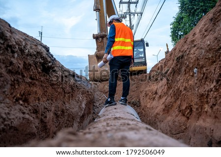 Engineer wear safety uniform examining excavation concrete Drainage Pipe and manhole water system underground at construction site.
