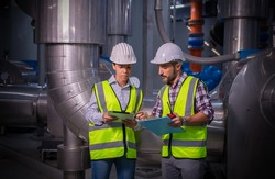 Engineer wearing safety uniform under checking the industry cooling tower air conditioner is water cooling tower air chiller HVAC of large industrial building to control air system.