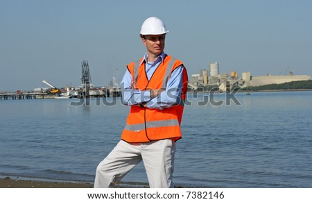 Engineer with arms folded wearing safety clothing at the mouth of the river with the docks in the background, the beautiful blue river and fantastic blue sky.