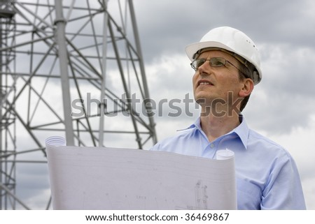 Engineer with blueprint in front of crane
