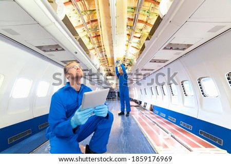 Engineer with digital tablet looking up at the wiring on the ceiling of an empty passenger jet with a coworker. Photo stock ©