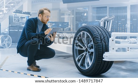 Engineer with Glasses and Beard Works on a Tablet Computer Next to an Electric Car Chassis Prototype with Wheels, Batteries and Engine in a High Tech Development Laboratory.