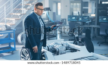Engineer with Glasses Works on a Tablet Computer Next to an Electric Car Chassis Prototype with Wheels, Batteries and Engine in a High Tech Development Laboratory.