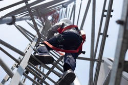 Engineer with safety equipment climb high tower for working telecom communication maintenance.