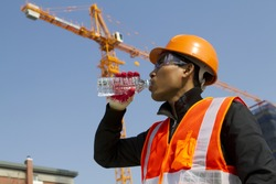 Engineer with safety vest drinking water under construction