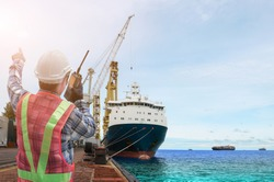 Engineer with walkie talkie in hand holding or portable radio transceiver for communication in shipping port export nautical vessel transportation and industry logistic and container ship sailing.