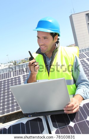Engineer with walkie-talkie on photovoltaic installation