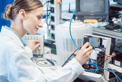 Engineer woman measuring electronic product on test bench in her lab for EMC compliance