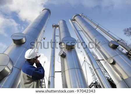 engineer, worker, pointing at giant gas and oil pipes