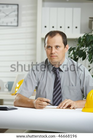 Engineer working at office - planning on blueprint on desk, looking away, thinking.