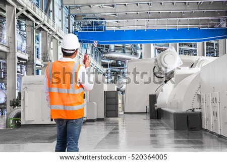 Engineer working in a thermal power plant with talking on the walkie-talkie for controlling work