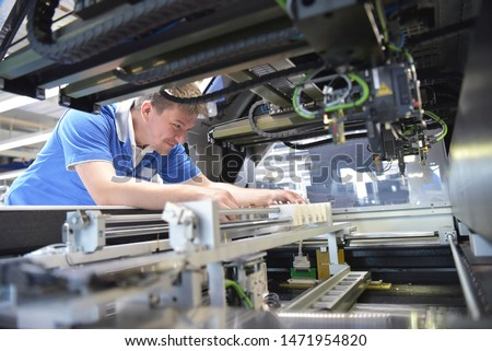 engineer working on a machine for assembly and production of semiconductor boards in an industrial plant