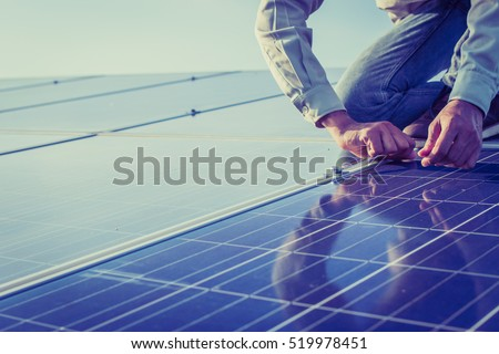 engineer working on checking and maintenance equipment at solar power plant: working on Wrench tightening solar mounting structure of solar panel  #519978451