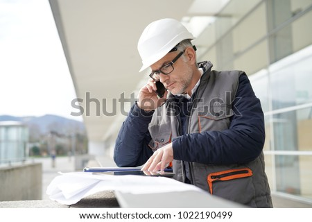 Engineer working on outdoor project and talking on phone  ストックフォト ©