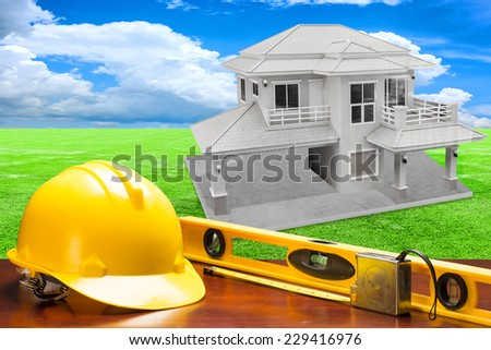 engineer working table and measure tape and level water tool equipment against house structure  in concept of real estate and engineering