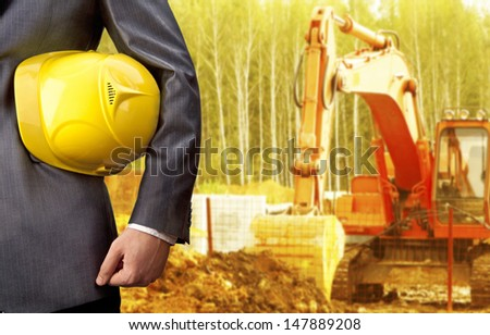 engineer yellow helmet for workers security against the background of the excavator bucket rake in a layer of earth