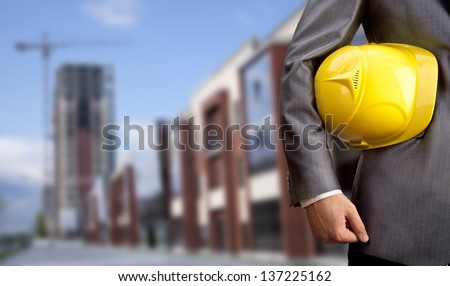 engineer yellow helmet for workers security on the background of a new high-rise apartment buildings and construction cranes and blue cloudy sky