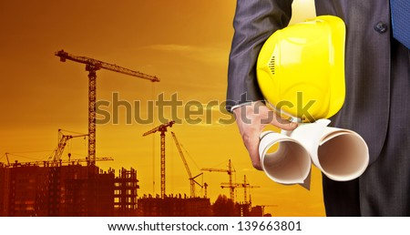 engineer yellow helmet for workers security on the background of a new high-rise apartment buildings and construction cranes and evening sunset sky
