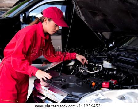 Engineering Asain woman checking car.