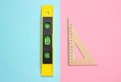 Engineering construction supplies on a pink blue pastel background. Construction level, ruler. Top view