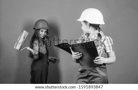 engineering idea. Future career. Labor day. 1 may. Little kids in helmet with tablet and roller. Foreman inspector. Repair. small girls repairing together in workshop. I need help. can you help me.
