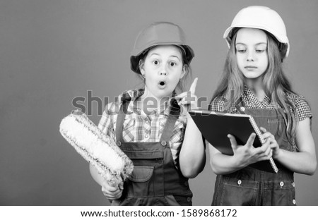 engineering idea. small girls repairing together in workshop. Labor day. 1 may. Little kids in helmet with tablet and roller. Foreman inspector. Repair. I think I know the problem.