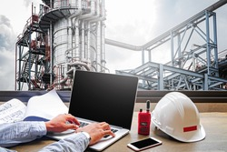 Engineering Industry concept in office with Oil and gas Industry,Refinery at sunset ,Pipelines and petrochemical plant background