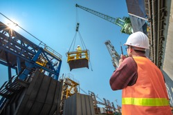 engineering, loading master connecting to gantry crane driver by walkie talkie for lifting safety in loading the goods or shipment, lifting by gantry crane, working at risk on the high level insurance