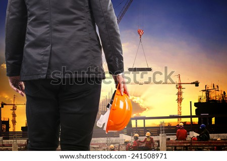 engineering man holding safety helmet and working in building construction site against  structure project site