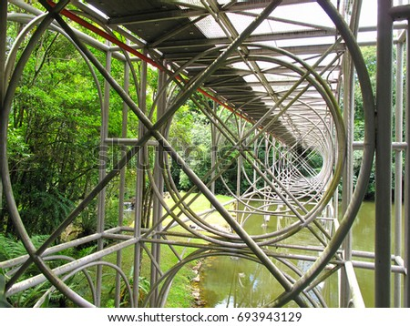 engineering marvel - circular steel wire frame supporting bridge structure over water #693943129
