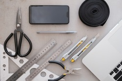Engineering or industrial designer work place, top view. Flat lay with laptop computer, smartphone, rope, scissors, rulers and knifes with grunge backdrop