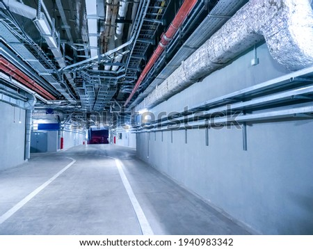 Engineering premises of  stadium. Auxiliary corridors for passage of special equipment. Place for passage of special equipment inside stadium. Spacious corridors of stadium with pipes under ceiling