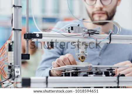 Engineering student using a 3D printer in the lab and printing a prototype