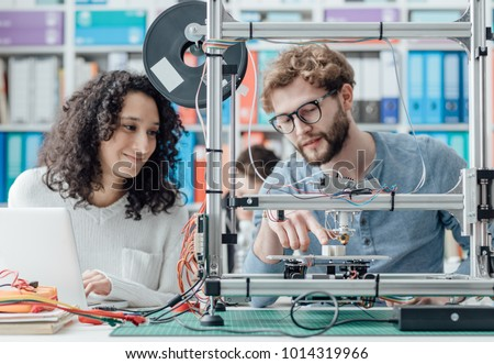 Engineering students using a 3D printer in the laboratory, they are using a laptop and printing prototypes