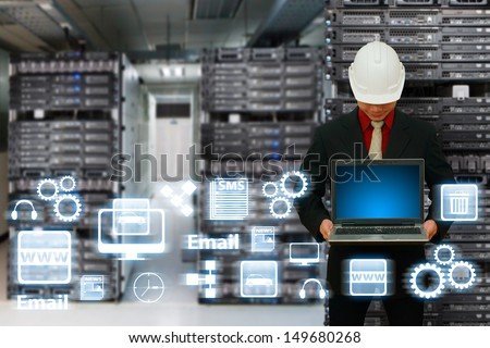 Engineering with laptop in data center room - stock photo