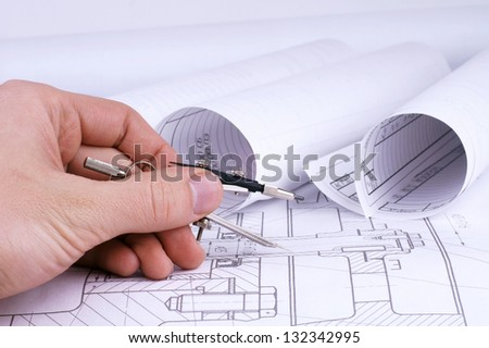 engineering work concept hand holding compass against background of blueprints and drawings