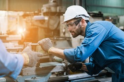Engineering worker man wearing uniform safety and hardhat working machine lathe metal in factory industrial, worker manufactory industry concept.