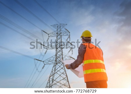 Engineering working on high-voltage tower, check the information on paper at sunset background