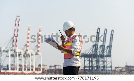 Engineers and crane.smiling dock worker holding radio and ship background