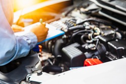 Engineers are checking cars. The light is golden at sunset.Blur image of young employees who are checking engines.Concept of quality inspection of cars Engine maintenance all the time.