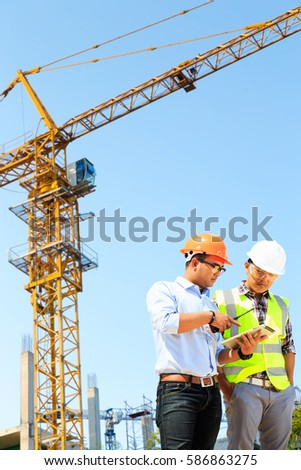 Engineers are working on the construction of the building crane.